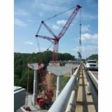 Two 1950s-era bridges on the Pennsylvania Turnpike/I-476, one over the Lehigh River and one over the adjacent Pohopoco Creek, are being replaced by four new spans by general contractor Walsh Construction Co. with the help of a 600-ton (660 US ton) Manitowoc 18000 lattice boom crawler crane from All Crane of Pennsylvania, a member of the ALL Family of Companies. The huge crane is carefully setting 70 165-foot precast concrete bridge beams for the Pohopoco spans on piers more than 100 feet above the creek.